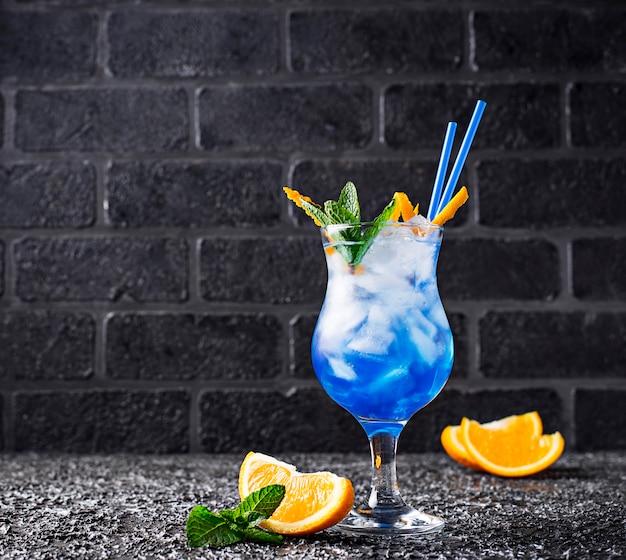 Blaues cocktailgetränk mit eis und orange