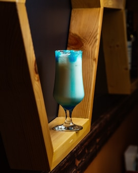 Blaues cocktailglas dargestellt in den hölzernen regalen