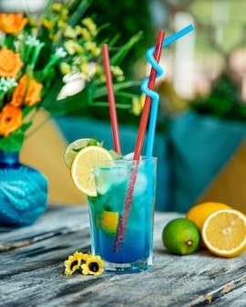 Blaues cocktailglas mit kalk und zitrone