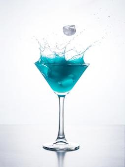 Blaues curaçao-cocktail mit spritzen
