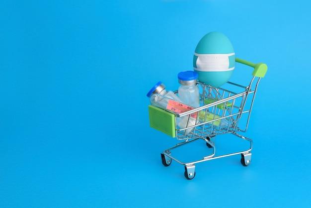 Blaues ei in der schützenden medizinmaske auf einkaufswagen mit thermometer und antibiotikaflaschen innen. glückliches coronavirus-osterkonzept. ostern in covid -19 quarantäne. speicherplatz kopieren. ostern 2020.