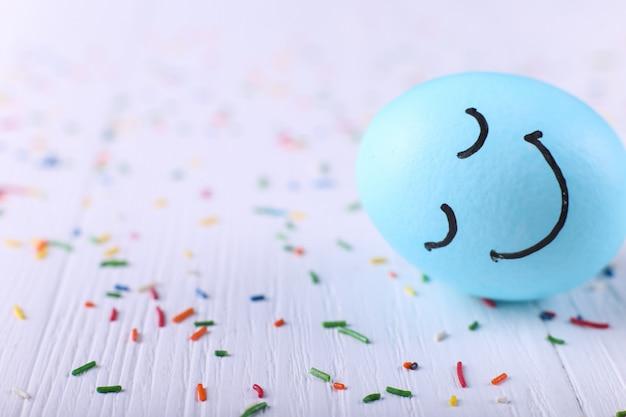 Blaues ei mit gemaltem lächeln glückliche ostern-grußkarte.
