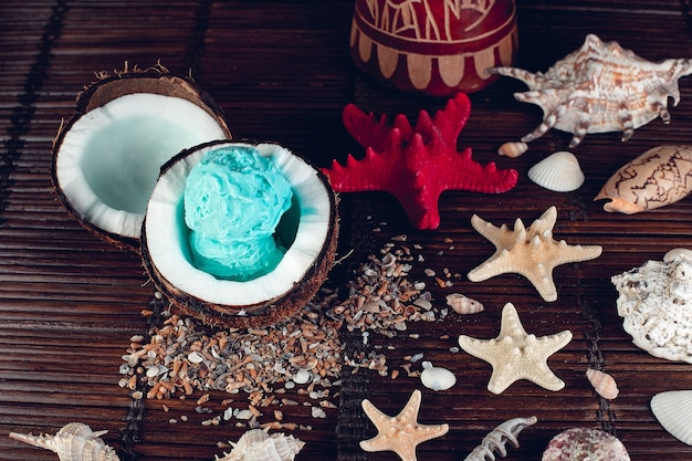 Blaues eis in der kokosnussschale nahe sand, muscheln, seestern.