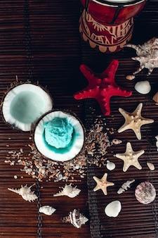 Blaues eis in kokosnussschale in der nähe von sand, muscheln, seesternen. ansicht von oben.