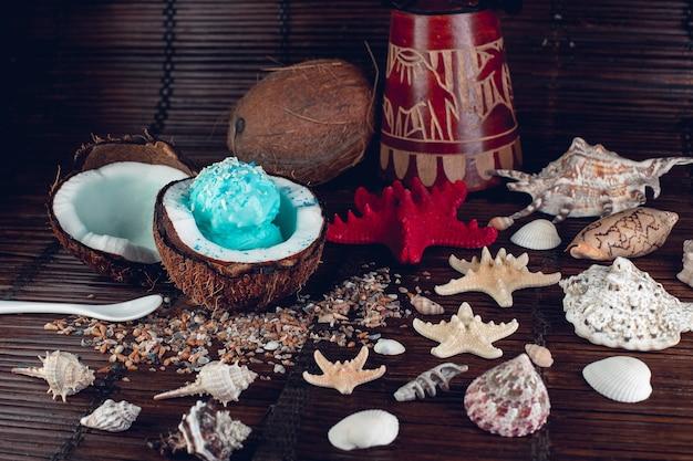 Blaues eis in kokosnussschale in der nähe von sand, muscheln, seesternen.