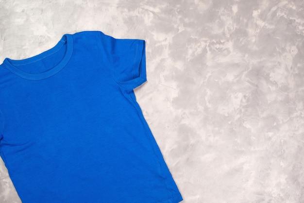 Blaues farb-t-shirt mit kopienraum. t-shirt modell, flach liegen. moderner konkreter hintergrund.