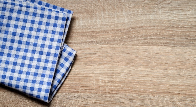 Blaues farbgewebe überprüfte tischdecke auf hölzerner beschaffenheits-tischplatte der weinlese in der küche