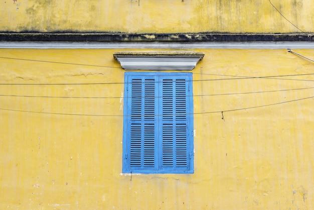 Blaues fenster auf gelber wand in hoi an