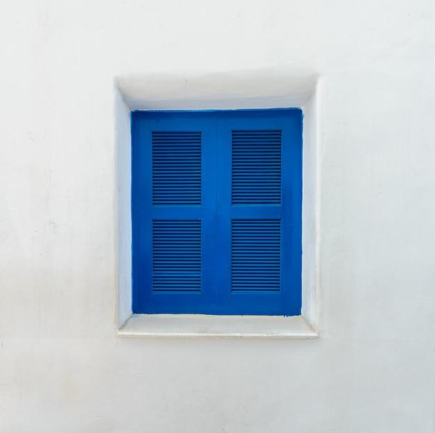 Blaues fenster auf weißer mittelmeerwand