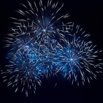 Blaues feuerwerk auf dem schwarzen himmelhintergrund