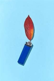 Blaues feuerzeug mit feuer aus herbstrotem blatt und harten schatten als handgemachte kreative komposition