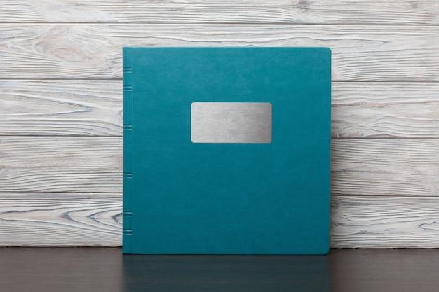 Blaues fotobuch auf einem holztisch