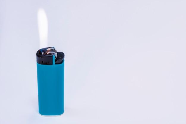 Blaues gasfeuerzeug, das mit feuer auf einem hellen hintergrund brennt.