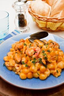 Blaues gericht mit gnocchi, meeresfrüchten und tomatensauce
