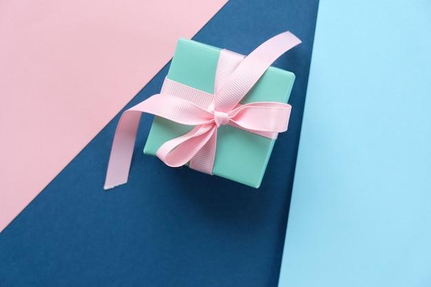 Blaues geschenk gebunden mit rosa band auf blauem hintergrund