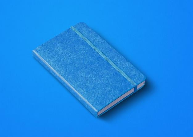Blaues geschlossenes notizbuchmodell lokalisiert auf farbigem hintergrund