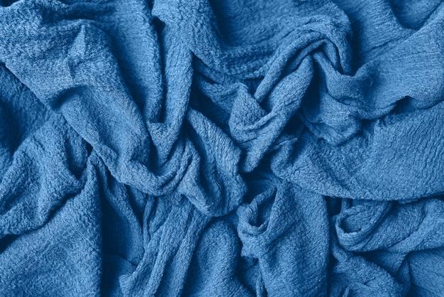 Blaues gestricktes jersey als textilhintergrund. modisches klassisches blaues farbtextule als farbe des konzeptes des jahres 2020. kopieren sie platz für text und design.