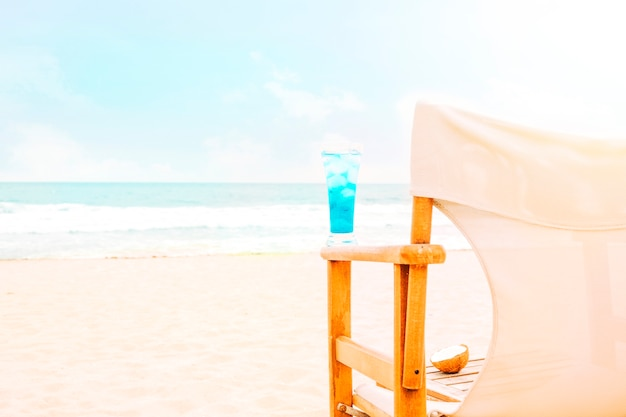 Blaues helles getränk auf arm des holzstuhls und der kokosnuss