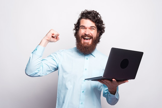Blaues hemd des bärtigen mannes, der laptop hält und sieg über weiße wand feiert