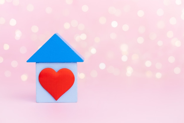 Blaues holzhaus mit rotem herzen auf rosa bokehwand mit kopienraum. konzept der süßen heimat.
