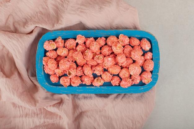 Blaues holztablett auf einer tischdecke, gefüllt mit aromatisiertem popcorn auf marmor.