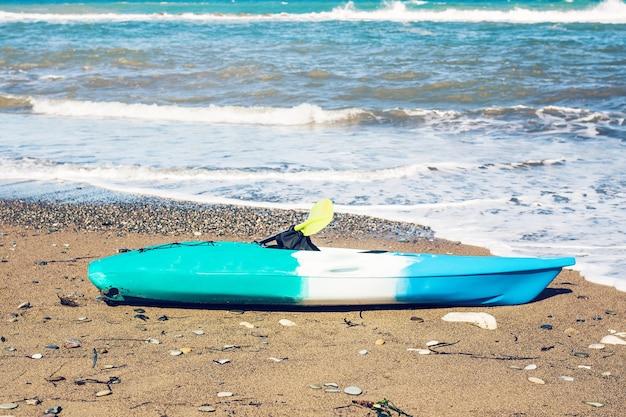 Blaues kajak, das auf dem sandstrand liegt