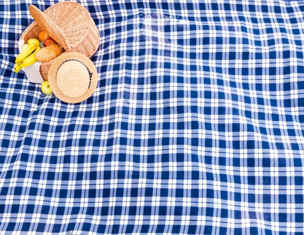 Blaues kariertes plaid mit strohhut- und picknickkorbhintergrund