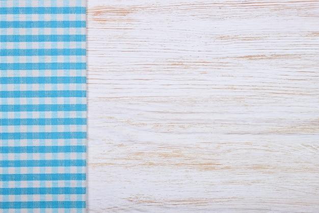 Blaues kariertes tischtuchtextil auf weißem holztischhintergrund. draufsicht, flach mit kopierraum, banner