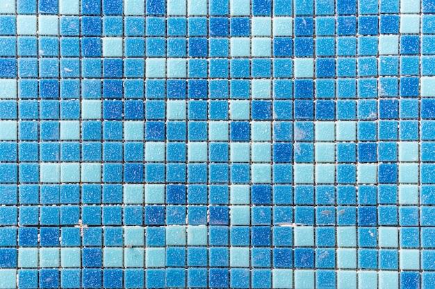 Blaues keramikmosaik im pool. verlegen von kleinen fliesen im pool. nahaufnahmehintergrund. bauarbeiten im pool.