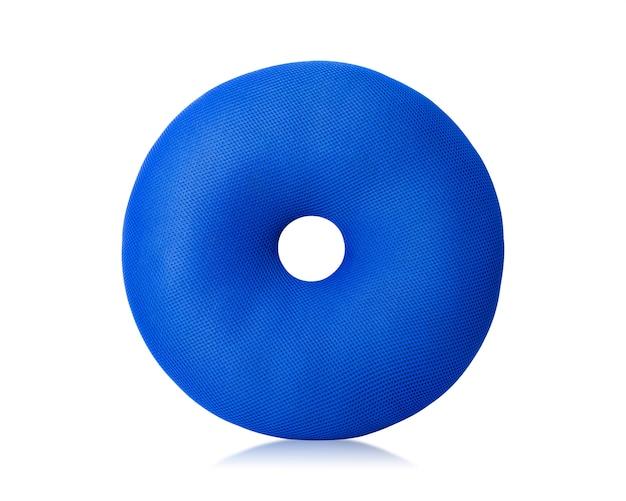 Blaues kissen mit der schaumgummiringform lokalisiert auf weißem hintergrund.