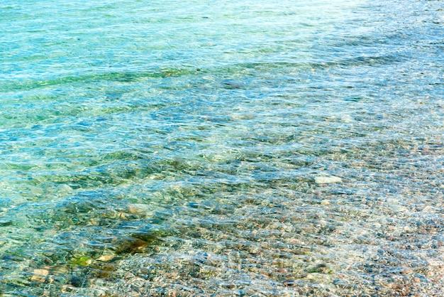 Blaues klares meerwasser am strand mit kieselsteinen