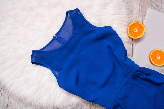 Blaues kleid und orangenhälften. weißes fell, modekonzept