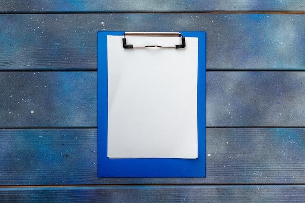 Blaues klemmbrett auf bürotisch, draufsicht, ebenenlage