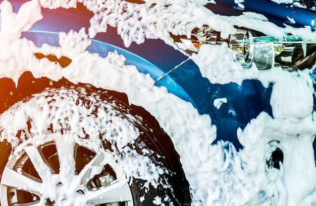 Blaues kompaktes auto mit sport und modernem design waschend mit seife.
