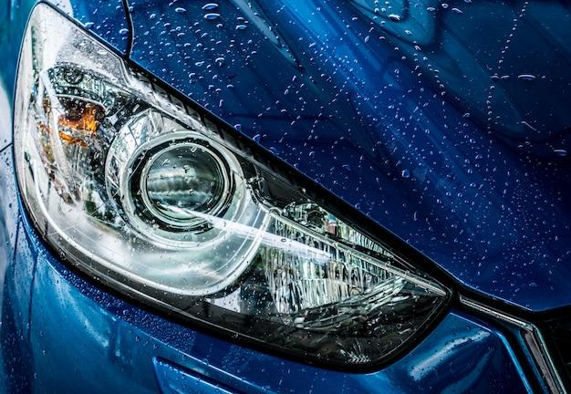Blaues, kompaktes suv-auto mit sport und modernem design wäscht sich mit wasser. autopflegedienst