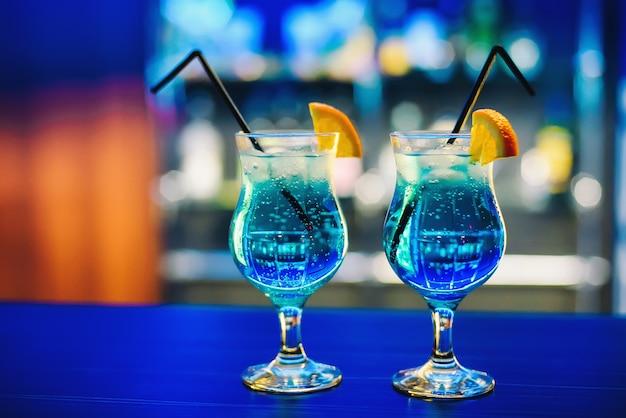 Blaues martini-cocktail im glas mit orange auf der bar köstlich und bunt mit alkohol