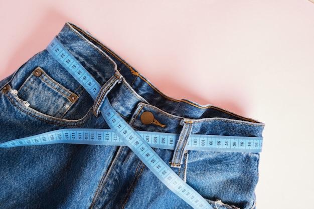 Blaues maßband wird in jeans anstelle eines gürtels eingefädelt, blaue jeans auf rosa hintergrund, kopierraum, gewichtsverlust und gewichtskontrollkonzept, messung des körpervolumens