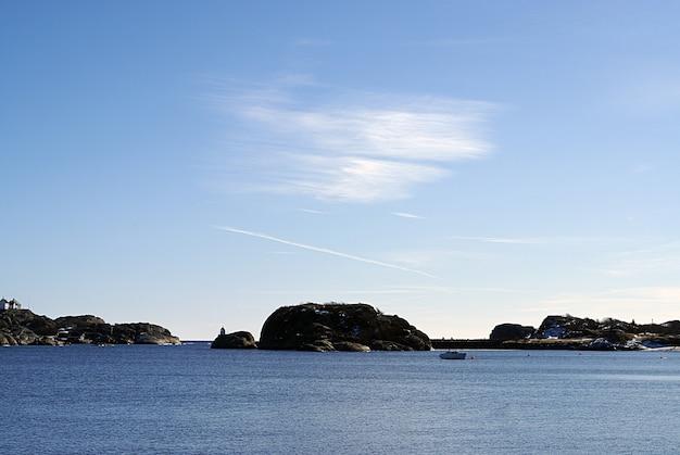 Blaues meer bei stavern, norwegen mit felsen im hintergrund