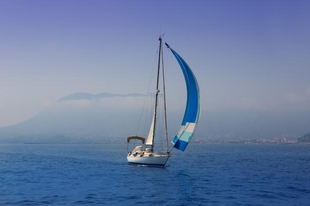 Blaues meer mit segelbootsegeln in einer nebeligen küste