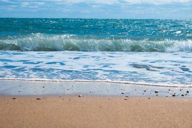 Blaues meer und strand mit goldenem sand. sommerferienhintergrund