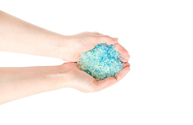 Blaues meersalz für ein bad in den händen eines mädchens lokalisiert auf weißer oberfläche.