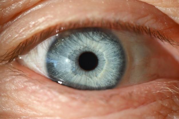 Blaues menschliches auge mit schwarzer pupillennahaufnahme. computer vision diagnosekonzept