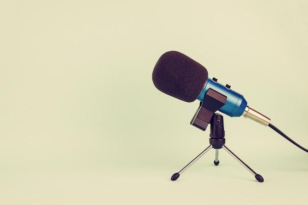 Blaues mikrofon mit draht auf pastellton im vintage-stil.