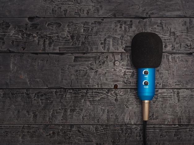 Blaues mikrofon mit draht auf schwarzem holztisch.