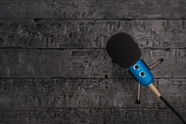 Blaues mikrofon mit schwarzem draht auf schwarzem holztisch.