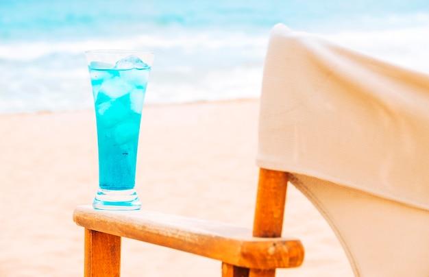 Blaues neues getränk auf arm des holzstuhls