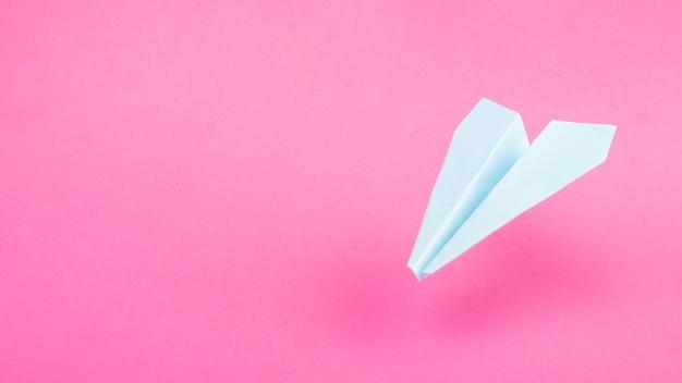 Blaues origami-flugzeug auf rosafarbenem hintergrund, reiseflüge kopieren raum.