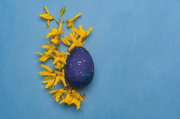 Blaues osterei mit gelben blumen auf einem blauen hintergrund.