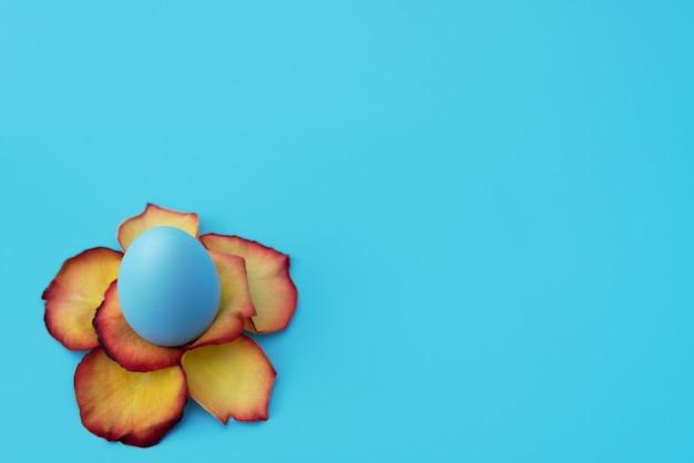 Blaues osterei steht in gelber blume aus rosenblättern auf blau