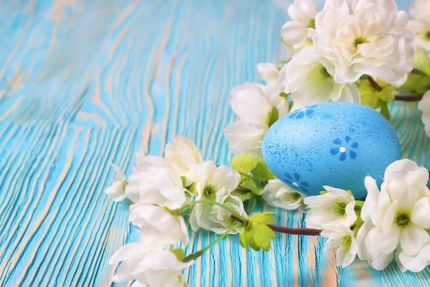 Blaues osterei und zweig mit blumen auf blauem holztisch